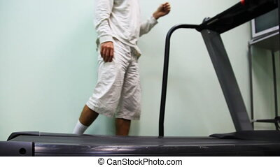 legs of man come on treadmill near wall in gym and begin go,...