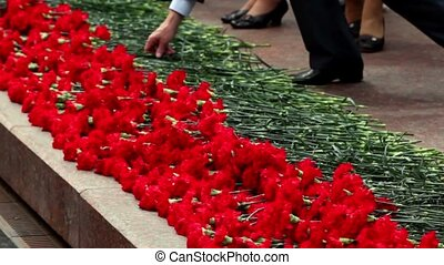 People put red flower on ceremony, only legs are visible