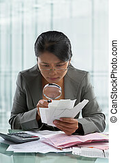 Asian businesswoman checking bills using magnifying glass in...