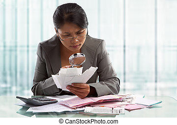 Asian businesswoman checking bills using magnifying glass