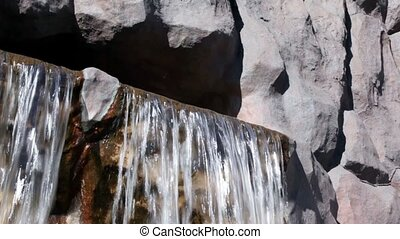 Waterfall streams from cave in wet rocks, closeup at sunny...