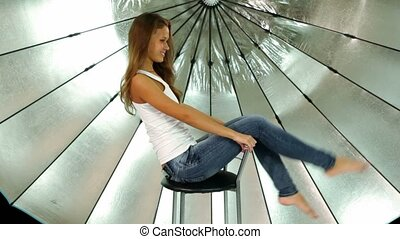 Girl sits on chair in front of reflector in photo studio -...