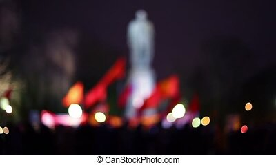 Crowd with red flags in front of monument at night,...