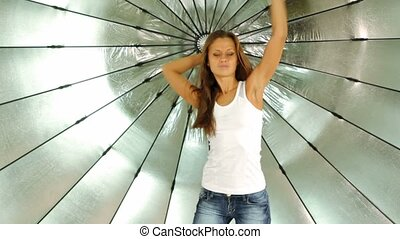 model in jeans and white shirt dances in front of reflector in photo studio