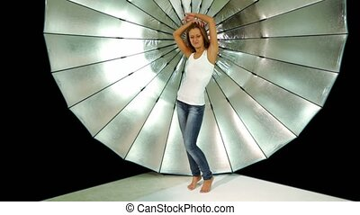 girl in jeans and shirt dances in front of reflector in photo studio