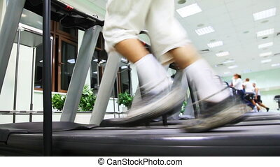 legs man run on one of many treadmill in large gym
