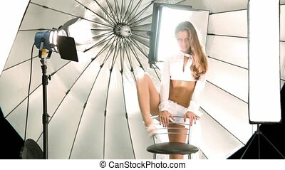 Young model put one leg on chair inside photo studio - Young...