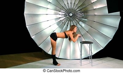 model make active movements by her legs in photo studio -...