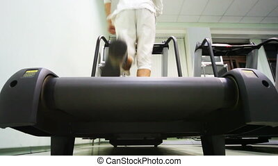 legs of man run on treadmill in empty gym, back view