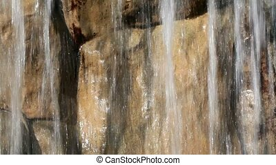 Waterfall streams, wet rocks, closeup at sunny day