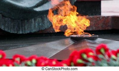 flowers lay near eternal fire on memorial grave of Unknown...