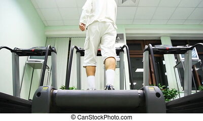 man stand at treadmill in gym, he turn on and begins go