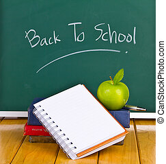 Back to school written on chalkboard with green apple and...