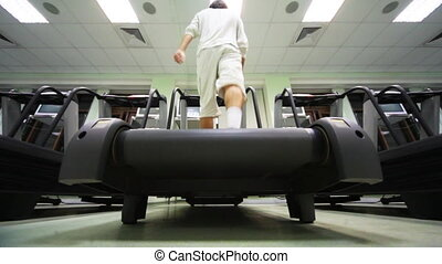 man goes on treadmill in big empty gym , bottom view