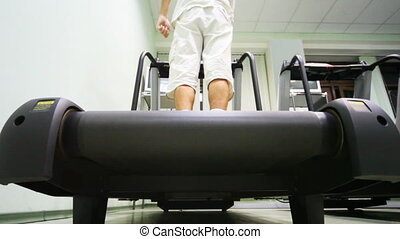 legs of man stand at treadmill in empty gym, he turn on and...