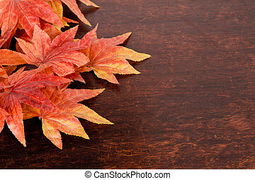 Artificial maple leafs over old wood background