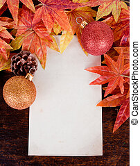 Christmas decoration and old paper with Artificial maple leafs over old wood background