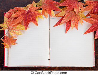 Open old book and Artificial autumn maple leafs