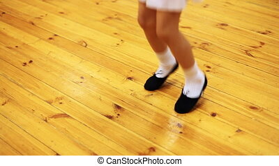 legs of little girl jump doing ballet movements on parquet