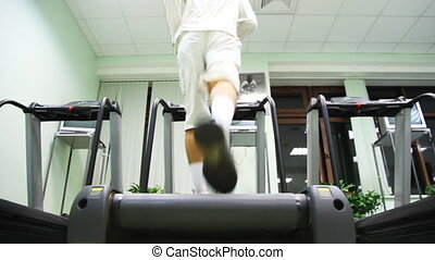 man runs on treadmill in large empty gym, back view