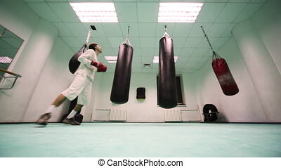 man in gloves jumps and punches on two large heavy punching...