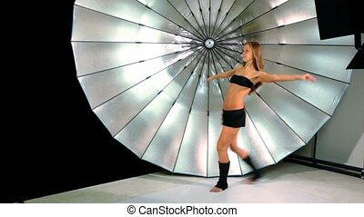 Young girl make active movements by her legs, in photo studio
