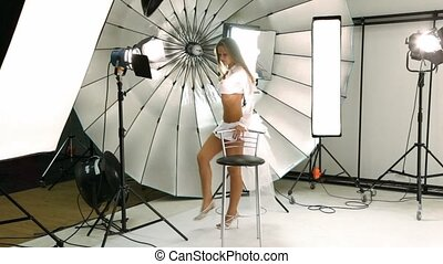 Girl walk around chair inside photo studio