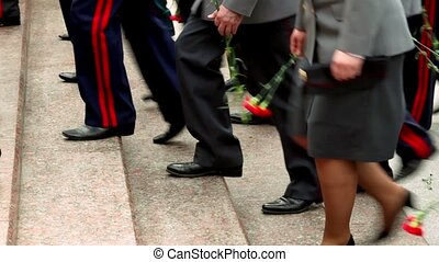 Military men ascend on stairs with red flowers, only legs...