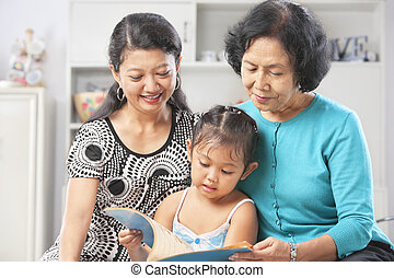 Little girl accompanied by mother and grandma reading book -...