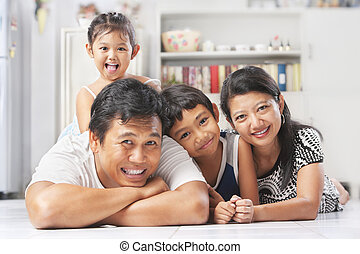 Asian family posing on the floor at home