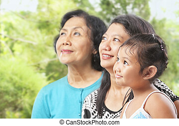 Three Asian female generations looking away at outdoor...