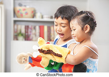 Asian sibling playing hand puppet - Asian sibling playing...