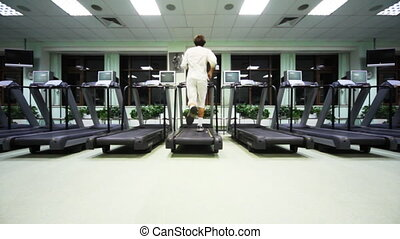 man quickly runs on treadmill in large empty gym, wide view