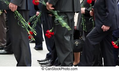 People ascend on stairs with red flowers, only legs are visible