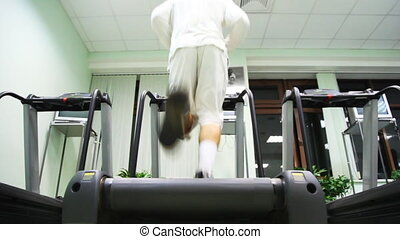 man quickly runs on treadmill in large gym, back view