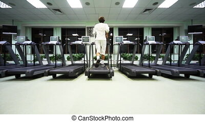 man runs on treadmill in large empty gym