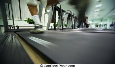 feet of man run on treadmill in large gym, distance train...