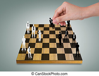 Hand Playing chess game with Silhouettes of business people