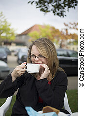 Young woman at cafe - Young woman enjoys a hot beverage at a...