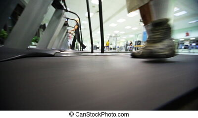 feet of man go on treadmill at large gym, distance in...