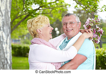 Love in spring - Happy mature woman looking at her husband...