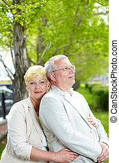 Couple in park - Mature woman looking at camera while...