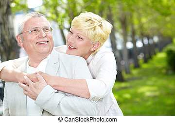 Couple in park - Portrait of happy mature woman hugging her...