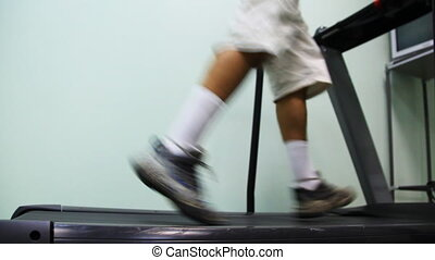 legs of man run on treadmill near wall in gym, side view