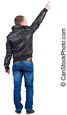 Back view of pointing  man in jeans and jacket.