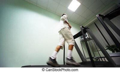 man runs on treadmill near wall in gym, bottom view