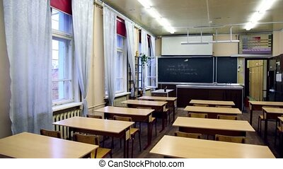 Chairs ant tables in physics school class, blackboard with...