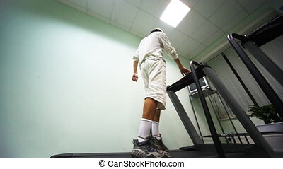 man stand at treadmill in gym, he turn on and begins go,...