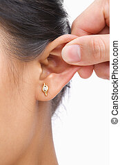 Finger pinching womans ear, over white background