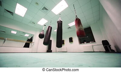 four different size punching bag hang in boxing training...